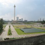 Merdeka Square view from Gambir Station upper platform. Jakarta's landmark Monas (National Monument) towering the square as the centerpiece, with reflecting pool and Kartini memorial on East Medan Merdeka park. Central Jakarta, Indonesia.