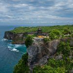 A rare perspective of Pura Luhur, a Balinese sea temple at Uluwatu on Bali, Indonesia. The temple sits on a sheer cliff, and guards Bali from evil spirits from the south-west.